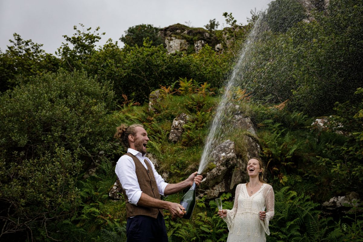 A newlywed couple fizz up a bottle of champagne before they toast their new marrige