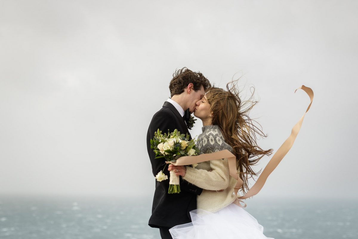 a bride and broom embrace during winter on the Isle of Skye. The bride is wearing a knitted sweater over her wedding dress